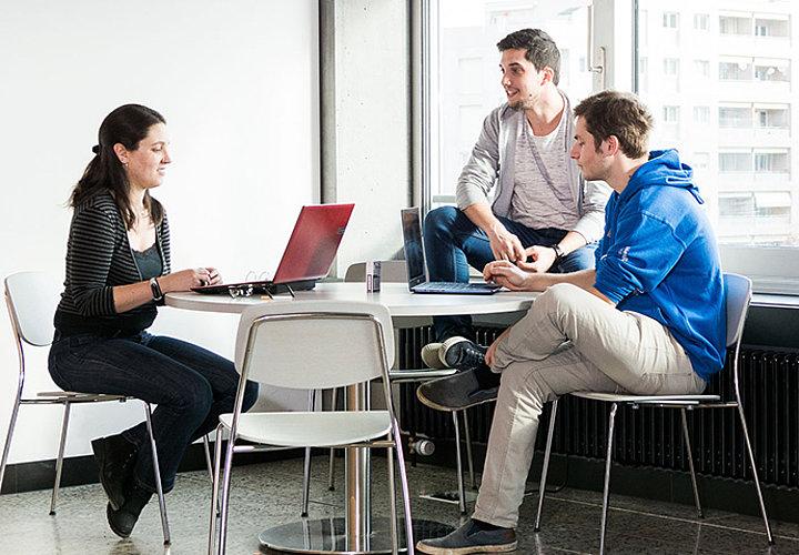 Une étudiante et deux étudiants travaillant sur leur ordinateur