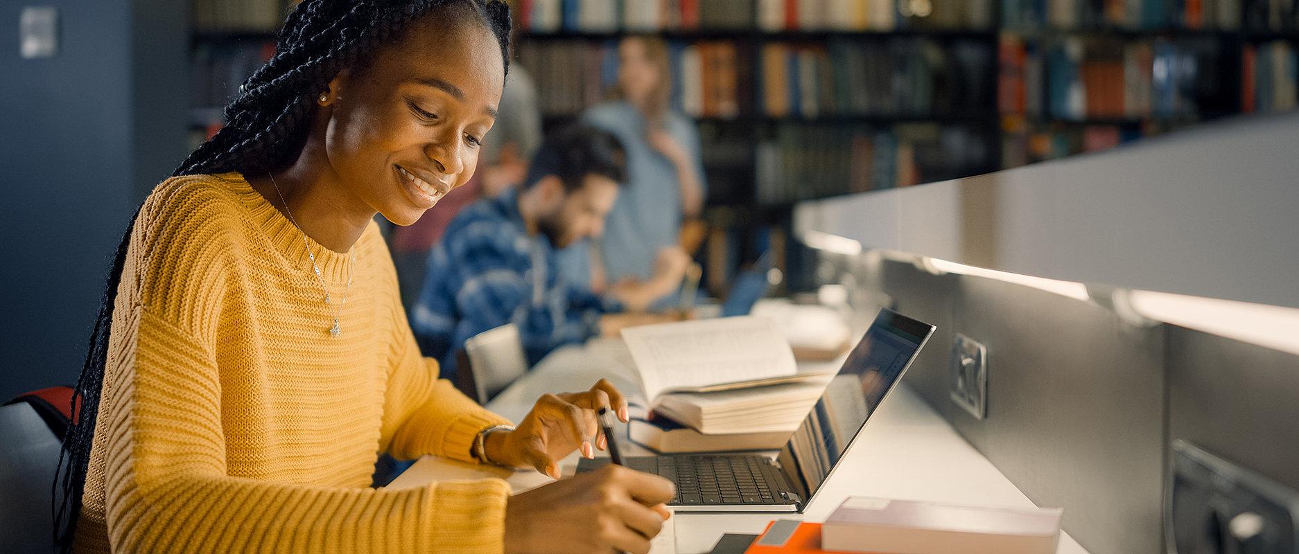 Etudiante en train de travailler dans une bibliothèque